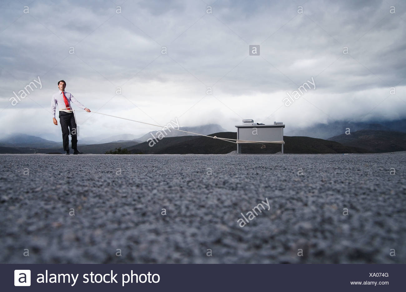 Man attempting to pull his desk outdoors with a long rope - Stock Image