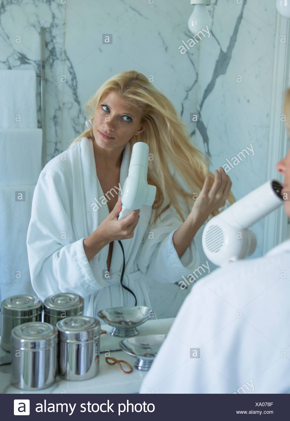Woman blow drying her hair in bathroom - Stock Image
