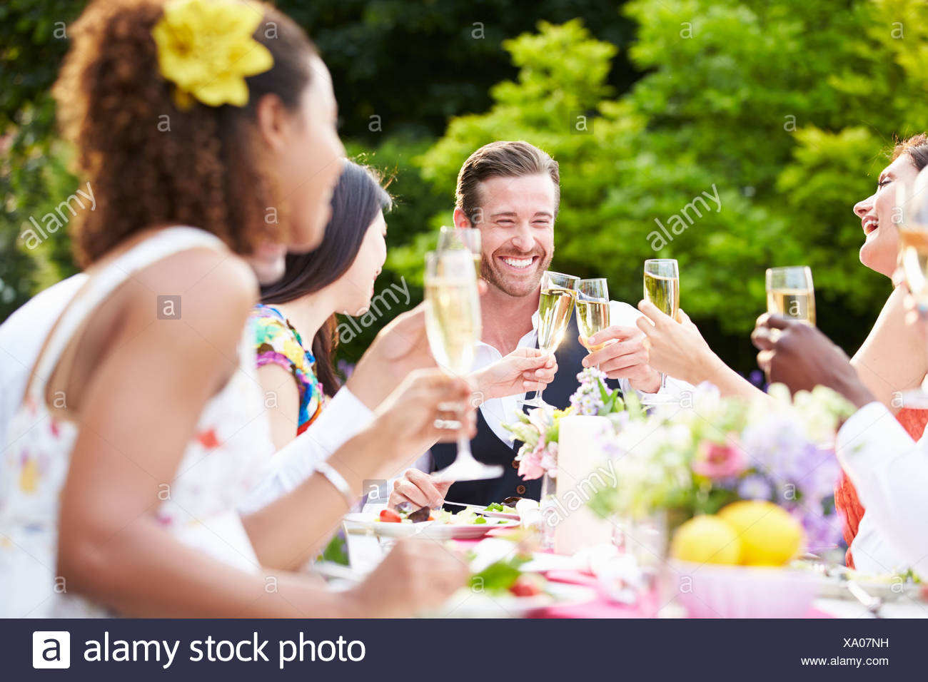 Group Of Friends Enjoying Outdoor Dinner Party Stock Photo