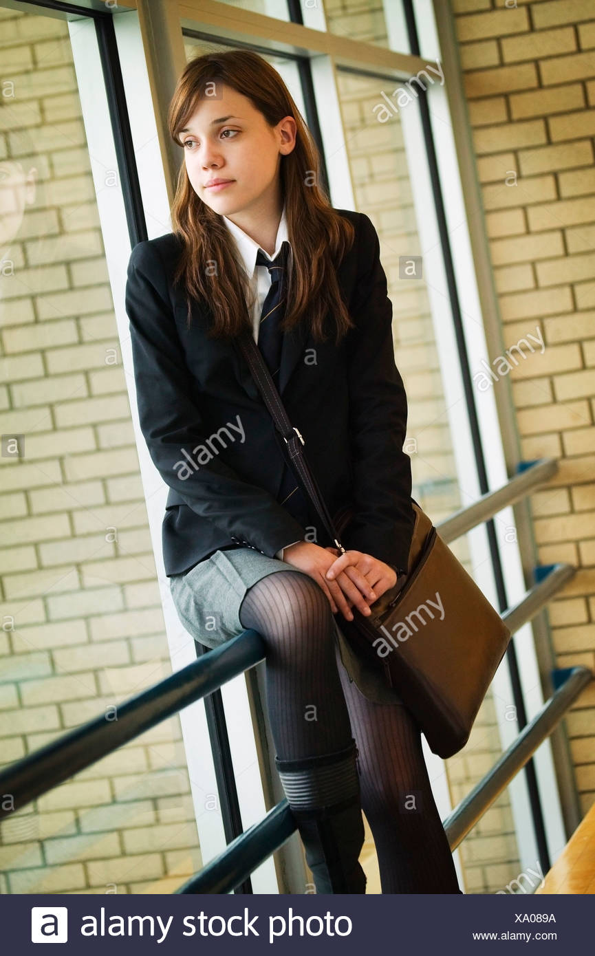 A student in uniform, seated on railing - Stock Image