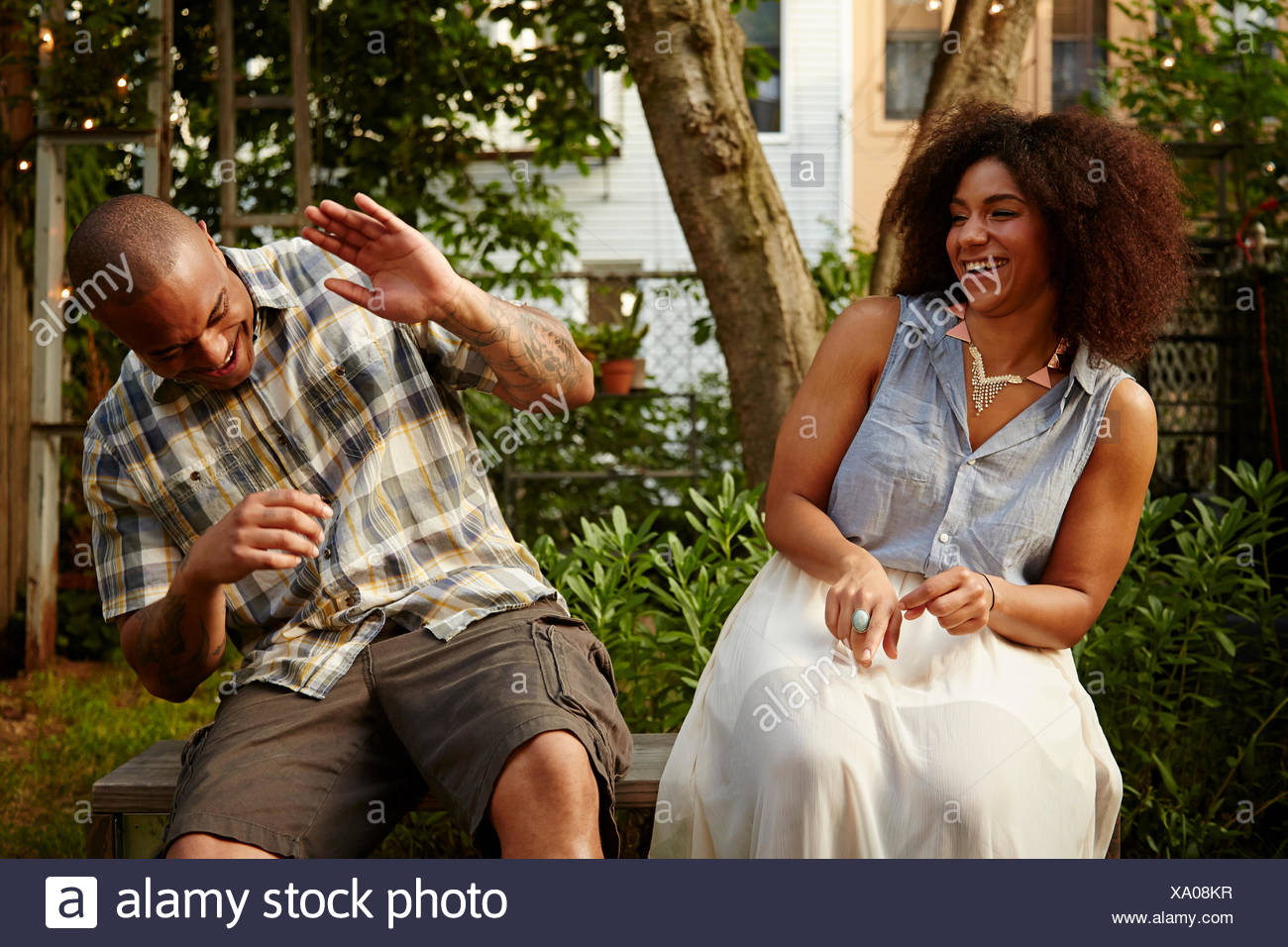 Mid adult man laughing with woman at garden party - Stock Image