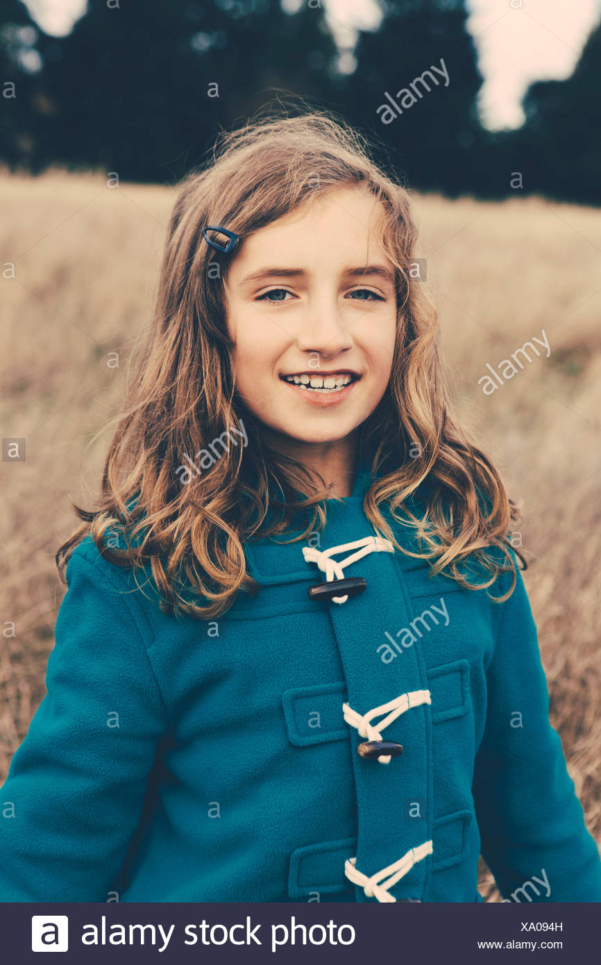 A young girl of nine years old, in a blue duffle coat, smiling at the camera. - Stock Image