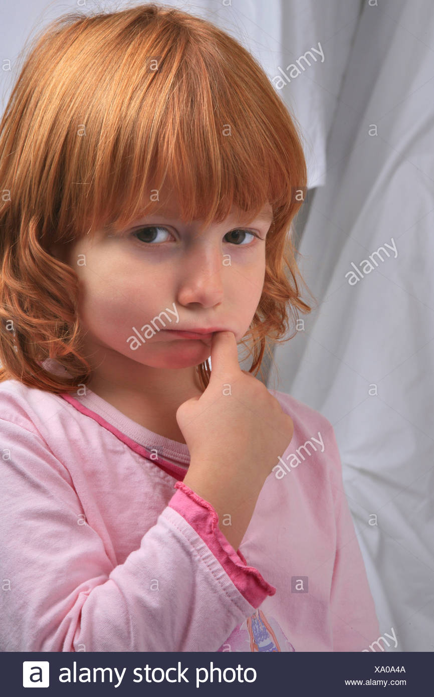 little redhaired girl in pyjama sulking doesn't want to go to bed - Stock Image