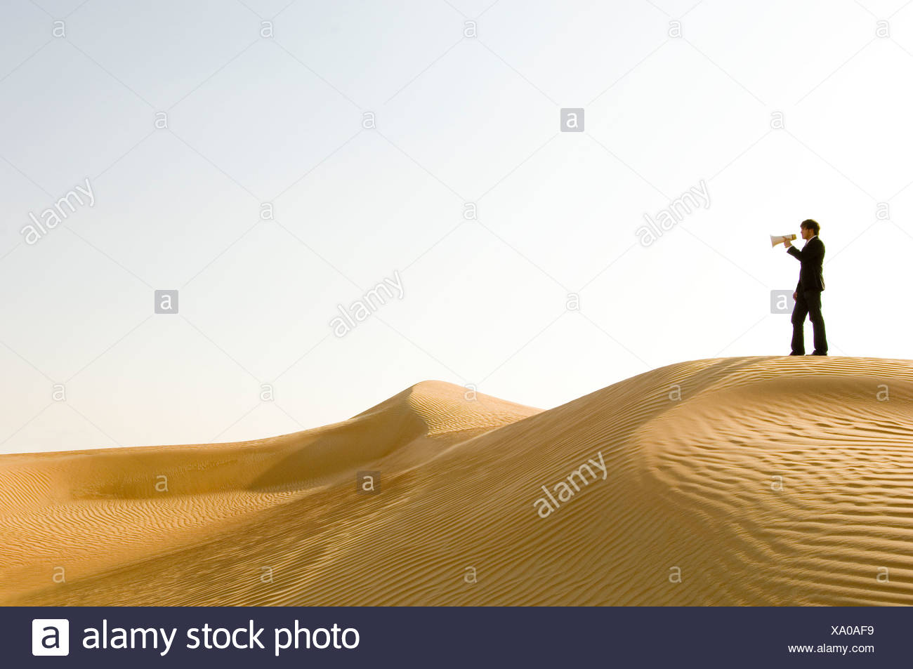 A young man standing in the desert with a loud hailer - Stock Image