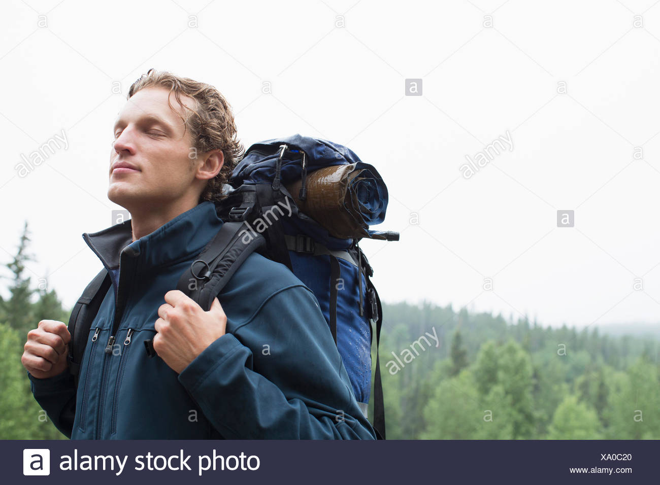 male backpacker breathing in fresh air with eyes closed - Stock Image