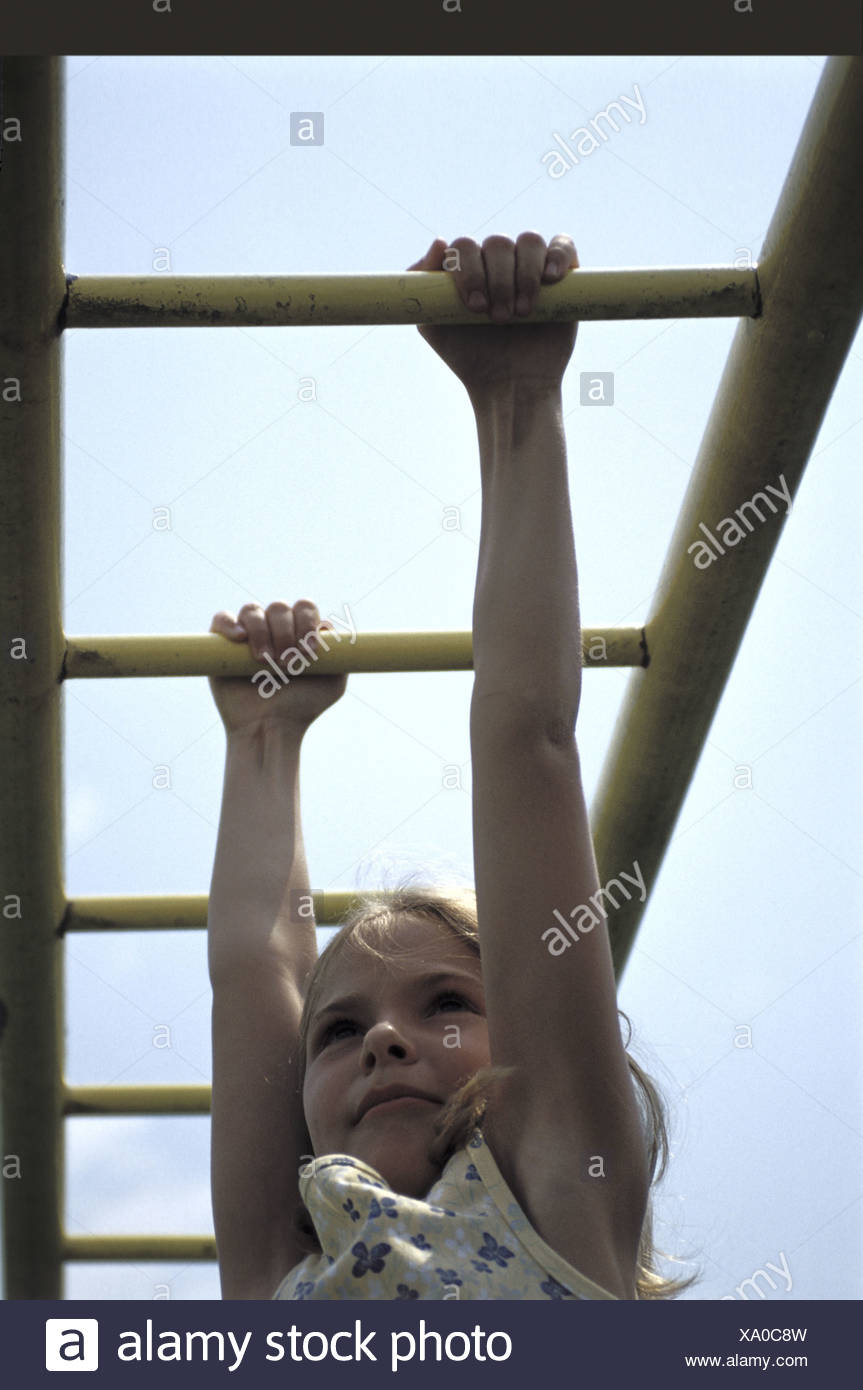 Low angle view of a girl hanging on monkey bars - Stock Image