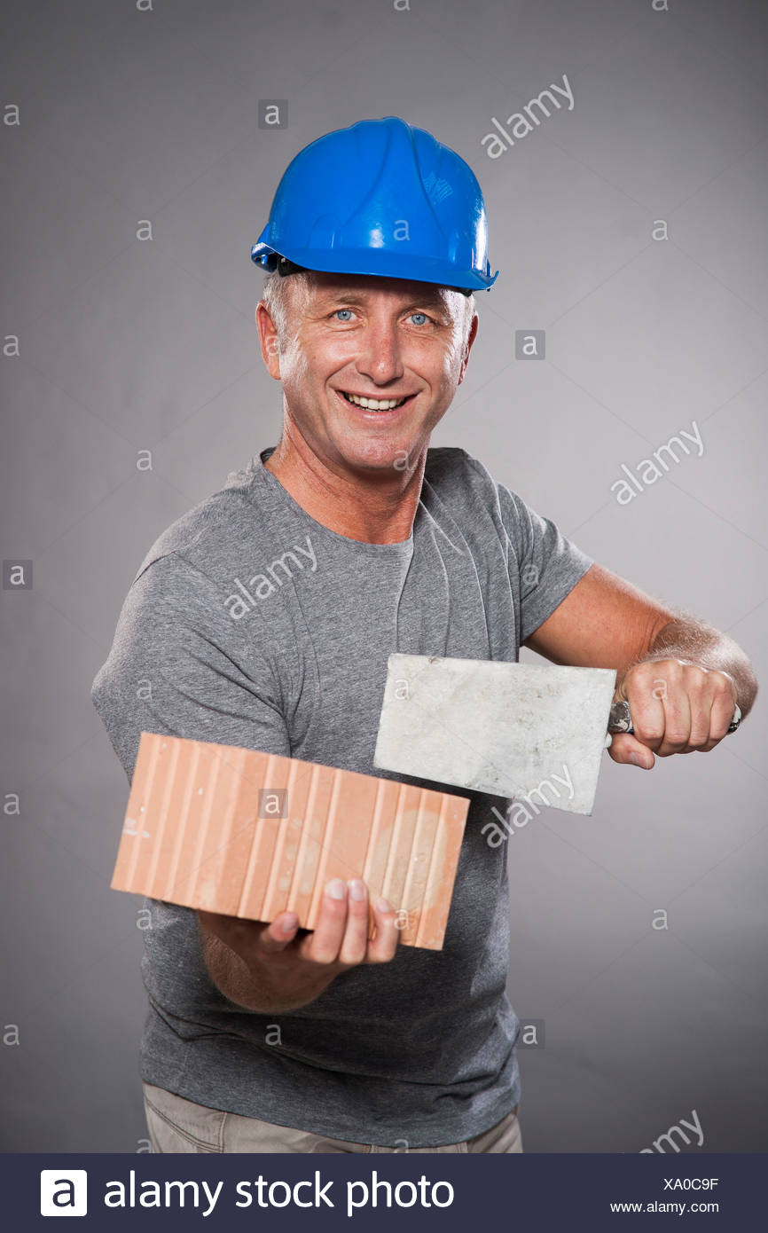 Construction worker wearing a hard hat, holding a trowel and a brick, Mannheim, Baden-Württemberg, Germany - Stock Image