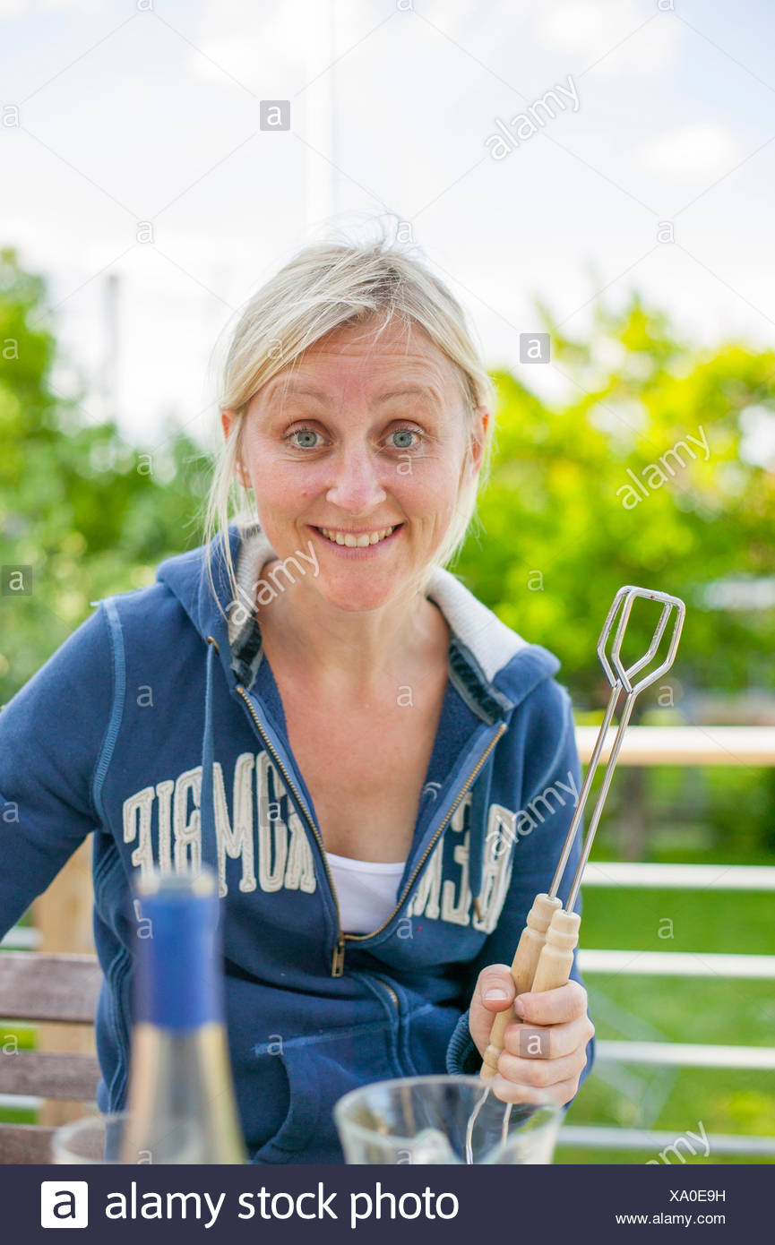 Sweden, Vastergotland, Lerum, Portrait of woman with barbecue tongs - Stock Image