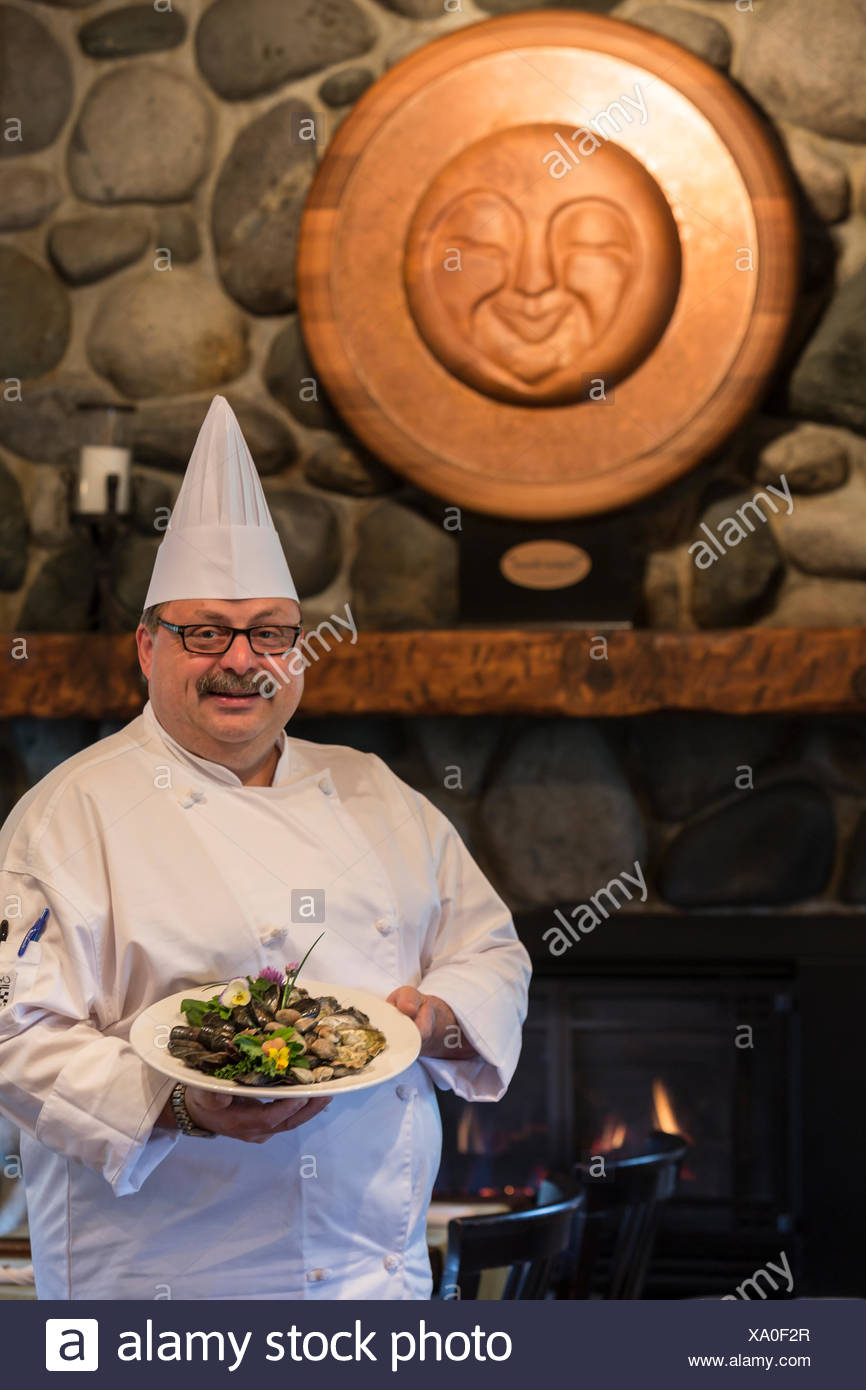 A chef inside his upscale restaurant presents a seafood dish, The Comox Valley, Canada - Stock Image