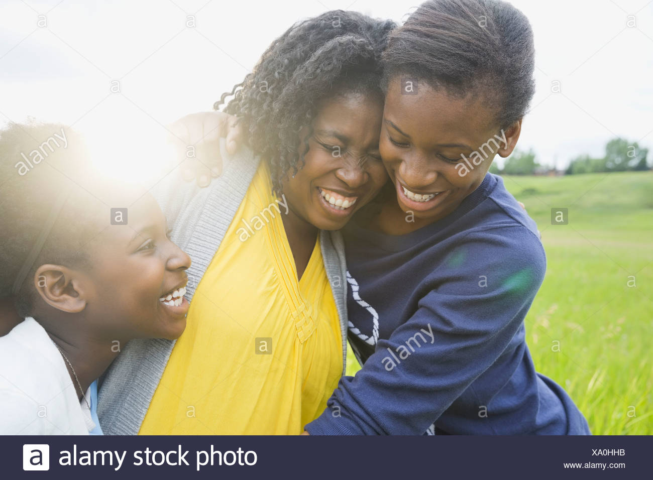 Cheerful mother and daughters hugging outside Stock Photo
