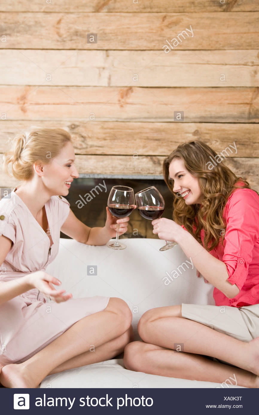 Two young women enjoying glass of wine - Stock Image