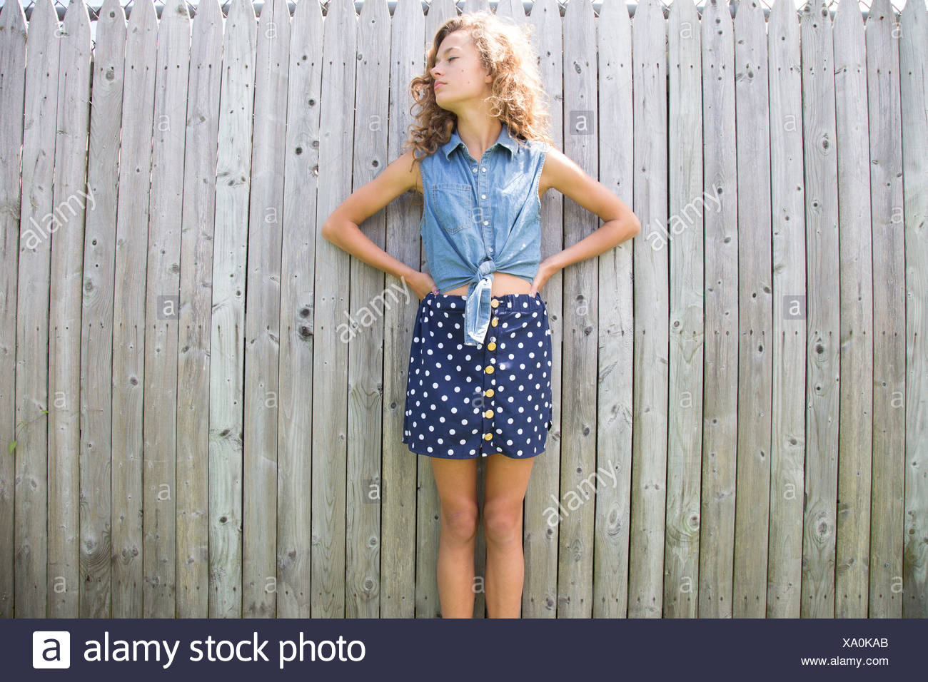 8f57be6b70f93 Portrait of teenage girl in front of wooden fence - Stock Image