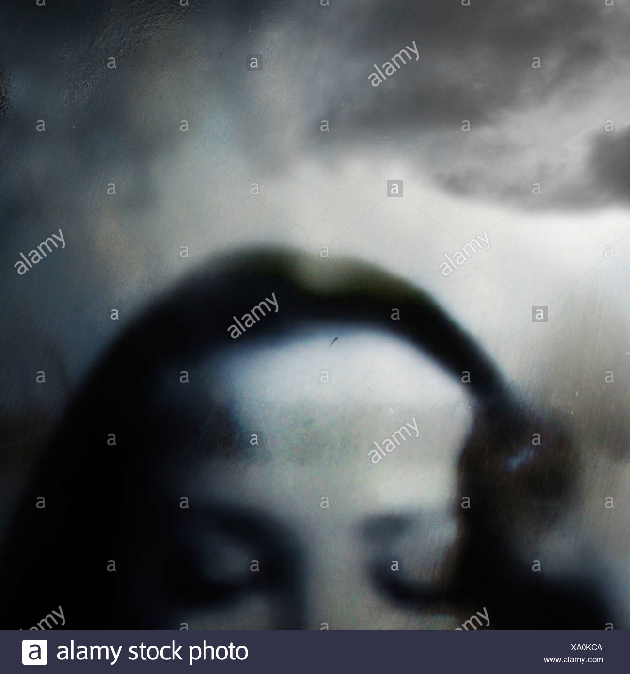 top half of a woman's head with eyes closed and clouds in the background - Stock Image