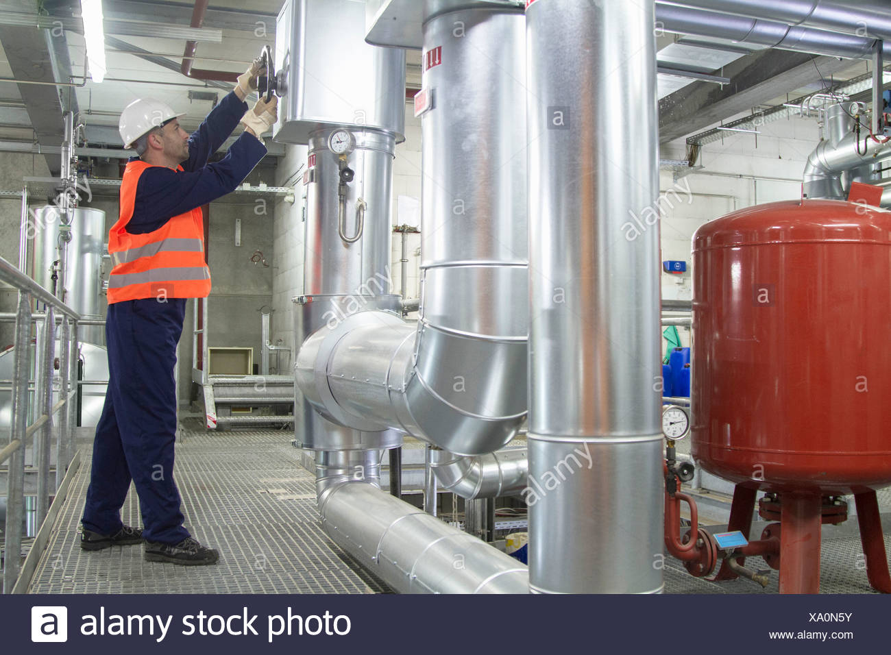 Technician reaching to check pipes in power station - Stock Image