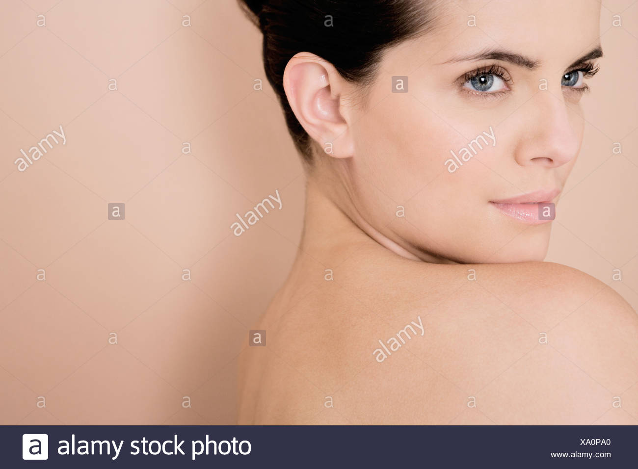 Portrait of a young woman looking over her bare shoulder - Stock Image