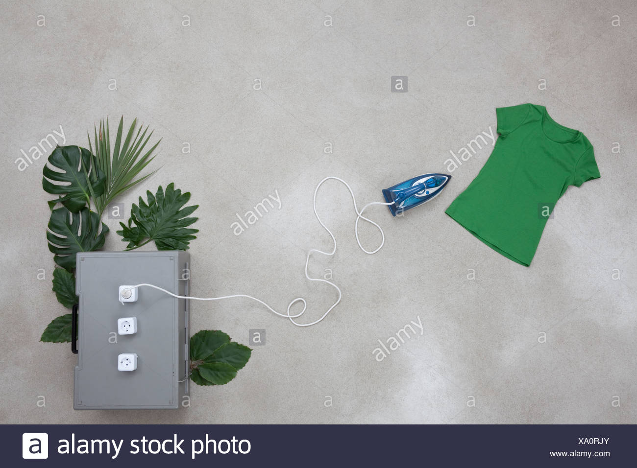 Iron connection to electric sockets with leaves, t-shirt on gray background Stock Photo
