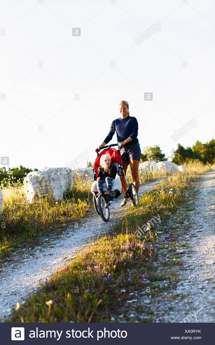 Sweden, Gotland, Farosund, Mother pushing son (2-3) in stroller down hill - Stock Image