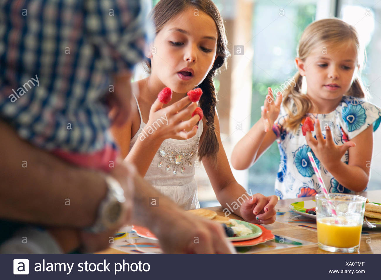 Two sisters with raspberries on their fingers at kitchen breakfast bar - Stock Image
