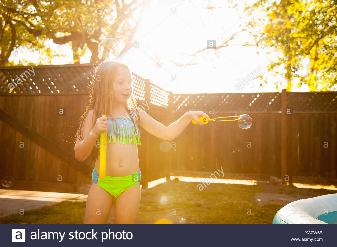 Girl making bubbles with bubble wand in garden Stock Photo