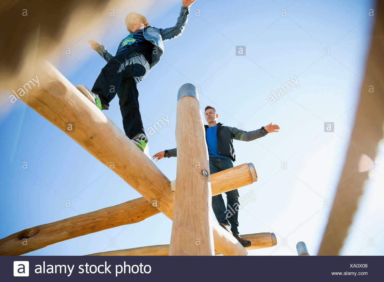 Father and son balancing logs sunny playground - Stock Image