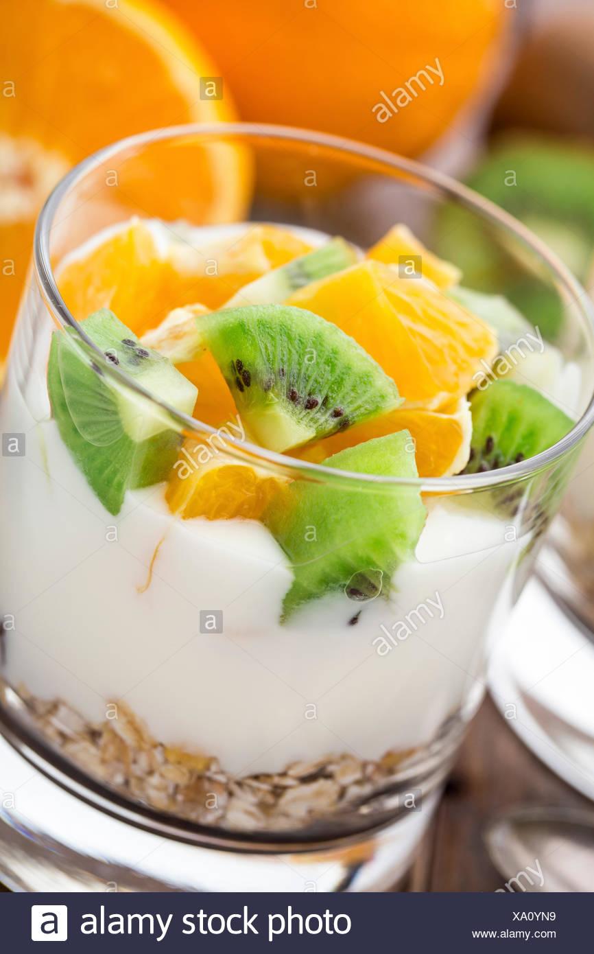 Yogurt with muesli, kiwi and orange in a glass - Stock Image