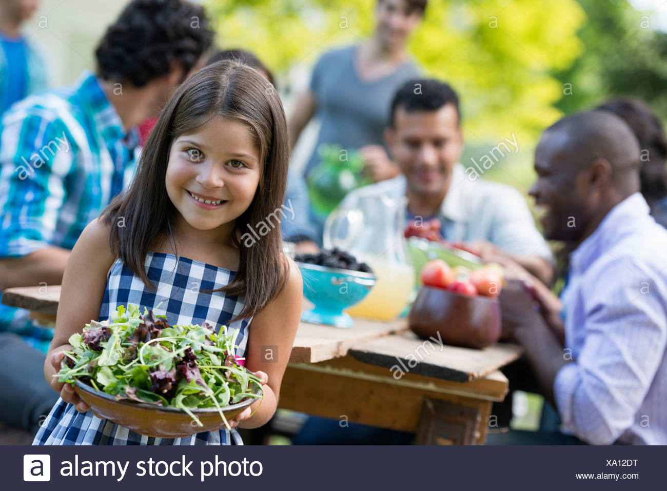 Adults and children around a table in a garden. A child holding a bowl of salad. - Stock Image
