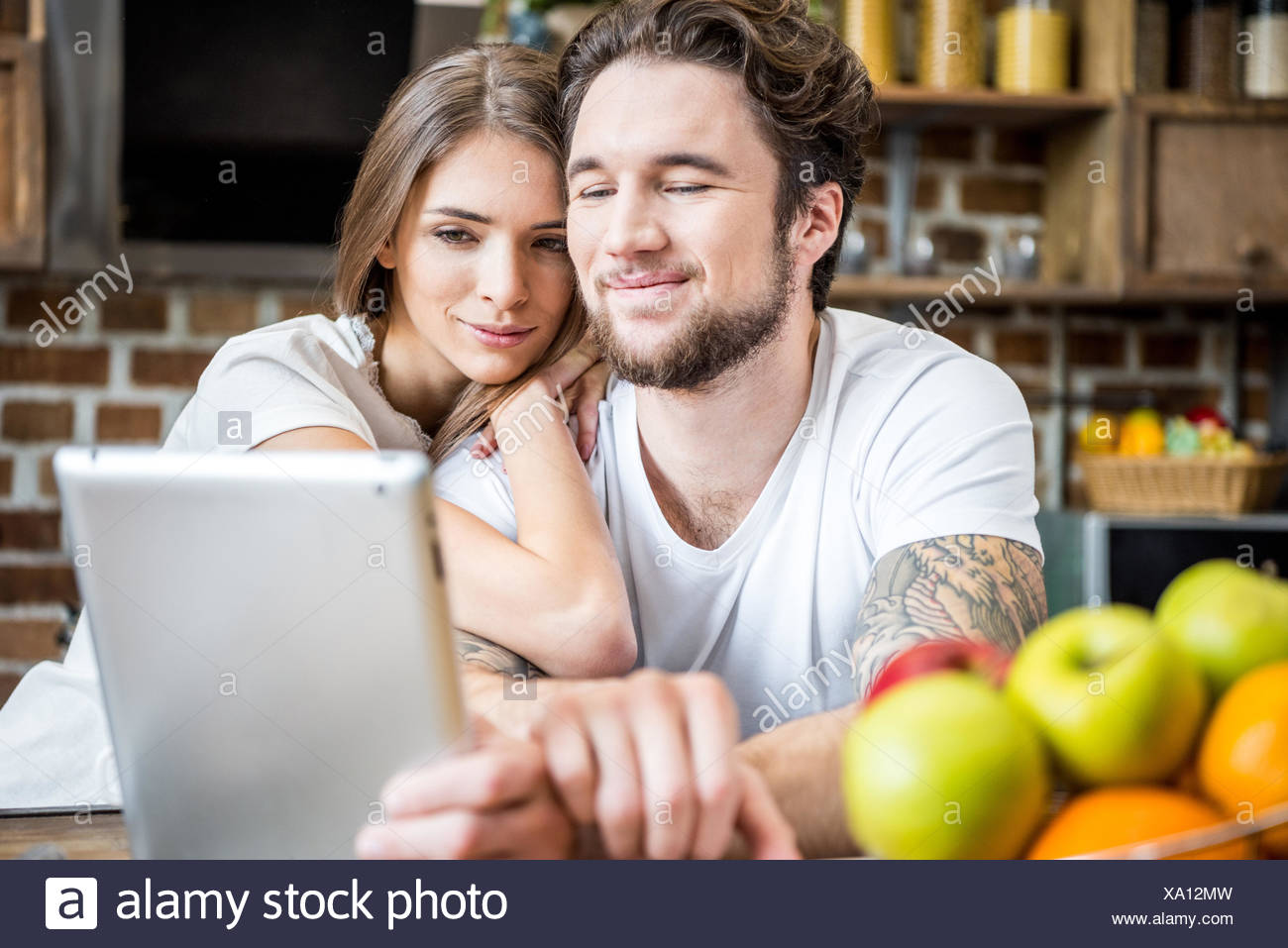 Couple using digital tablet at kitchen - Stock Image