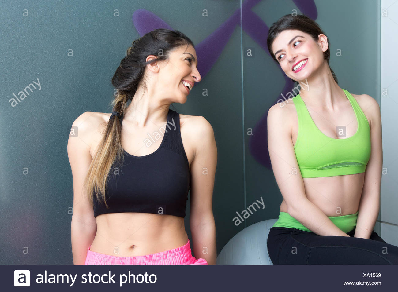 Two young women looking at each other and smiling in gym - Stock Image