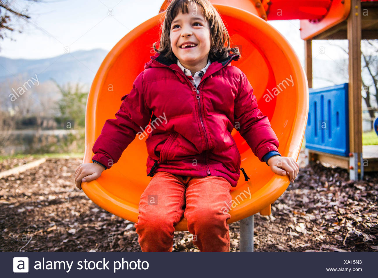 Boy sitting on orange playground slide - Stock Image