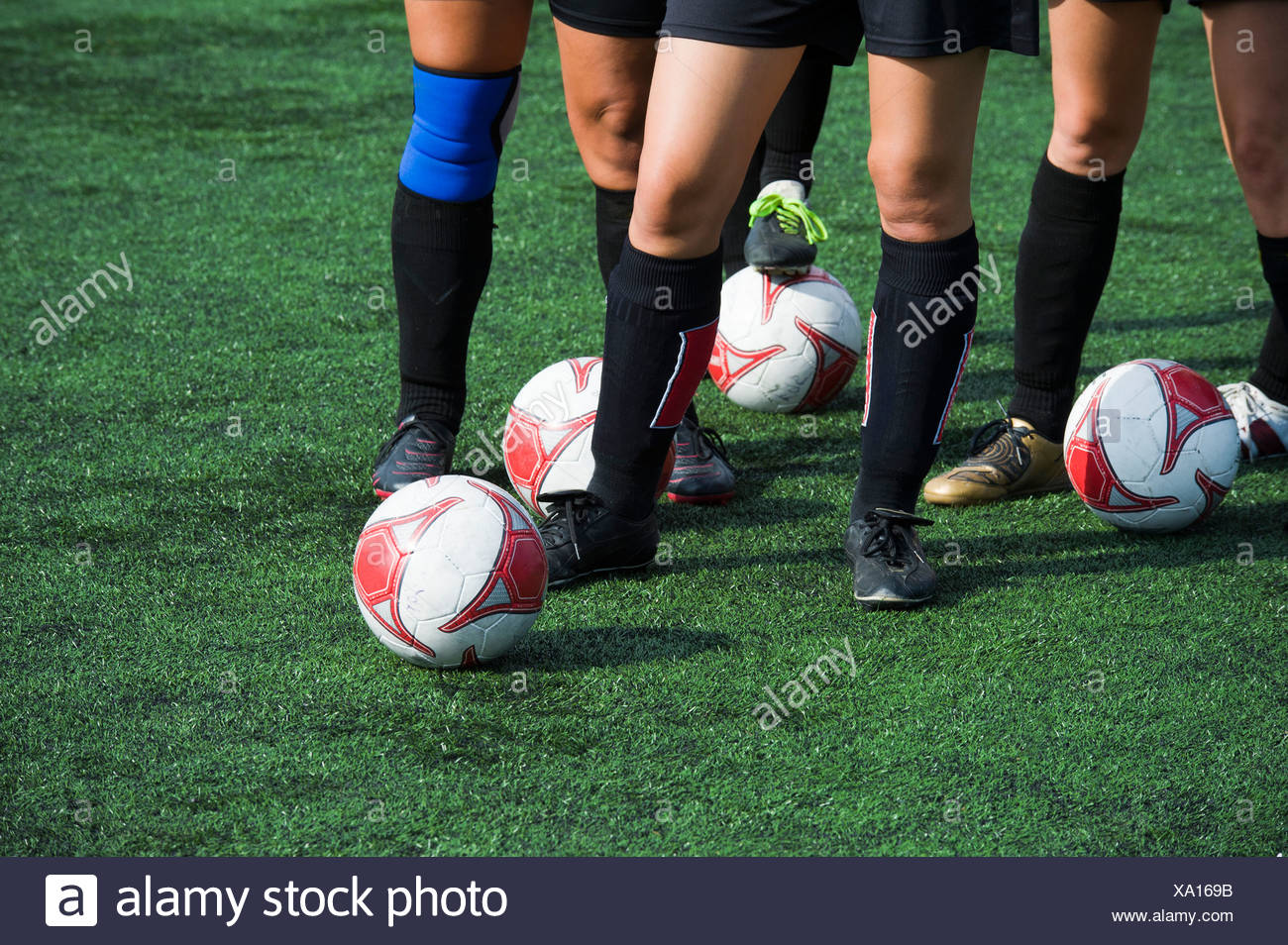 Low section of football players practicing on the grass - Stock Image