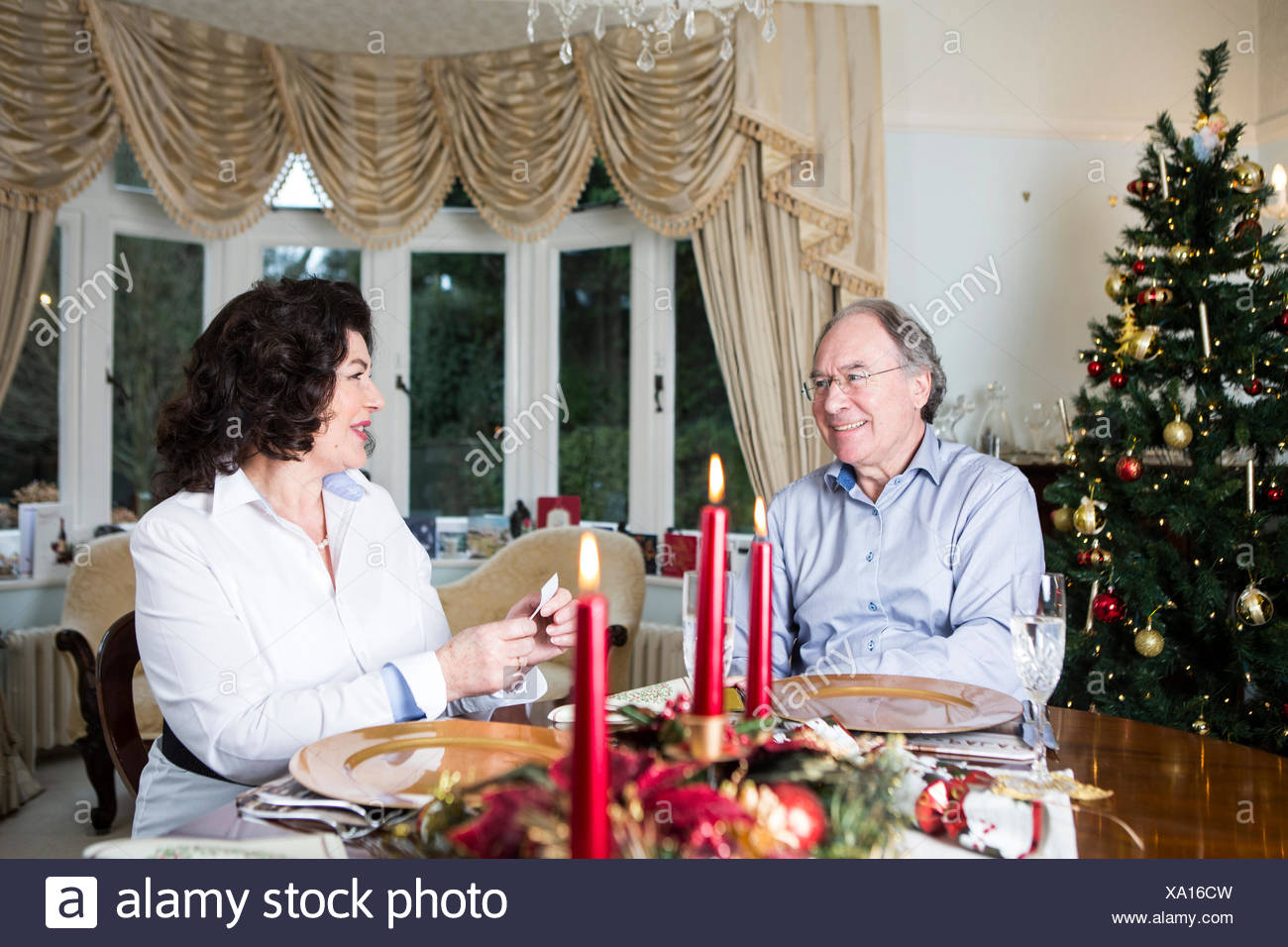Senior couple sitting at dining table on Christmas Eve - Stock Image