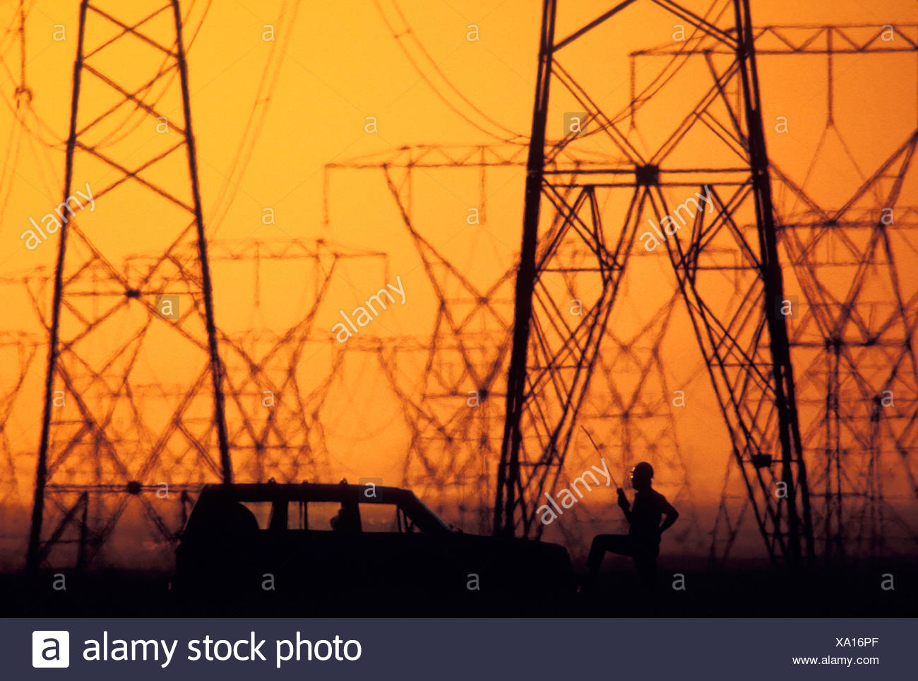 Silhouette of construction worker, car and electricity pylons with sunset in background - Stock Image