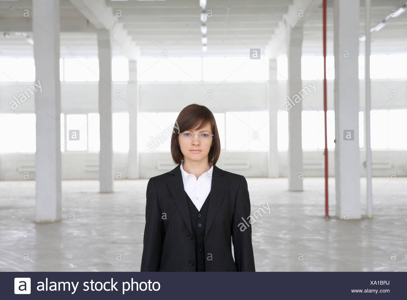 Business woman stands in empty warehouse - Stock Image
