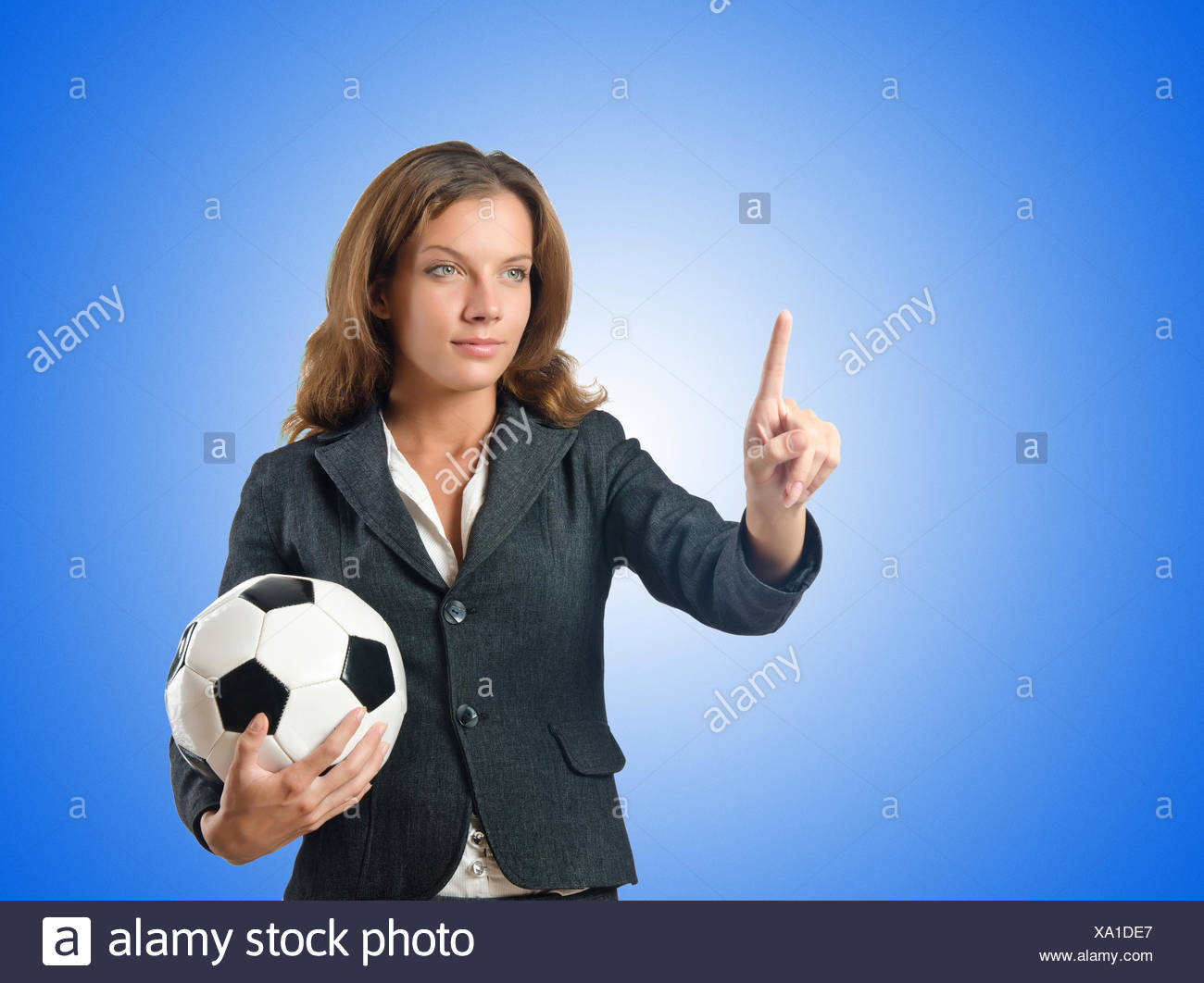 Businesswoman with football on white - Stock Image