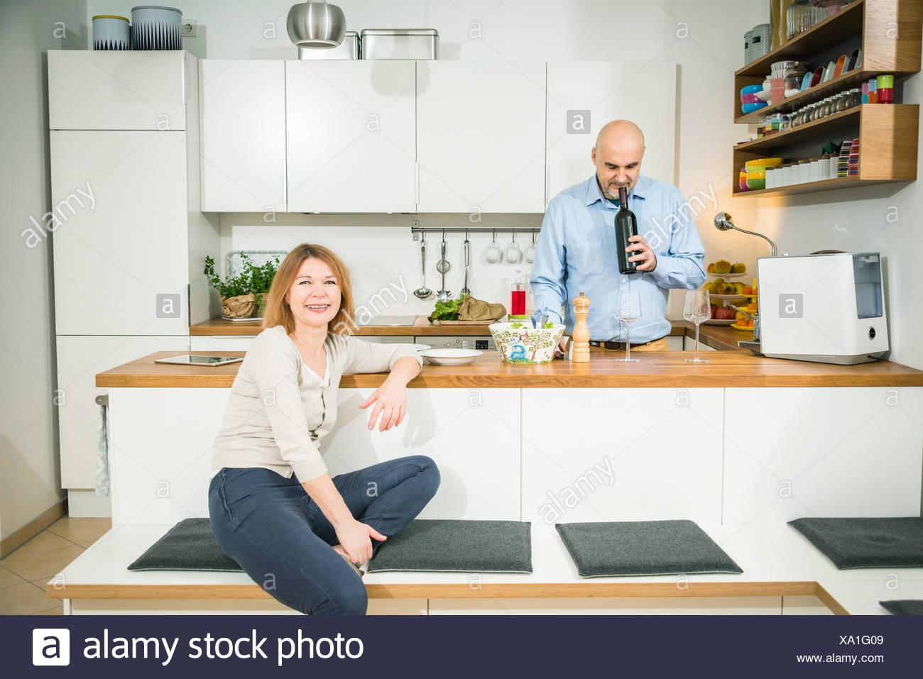 Senior man smelling wine cork in kitchen Stock Photo