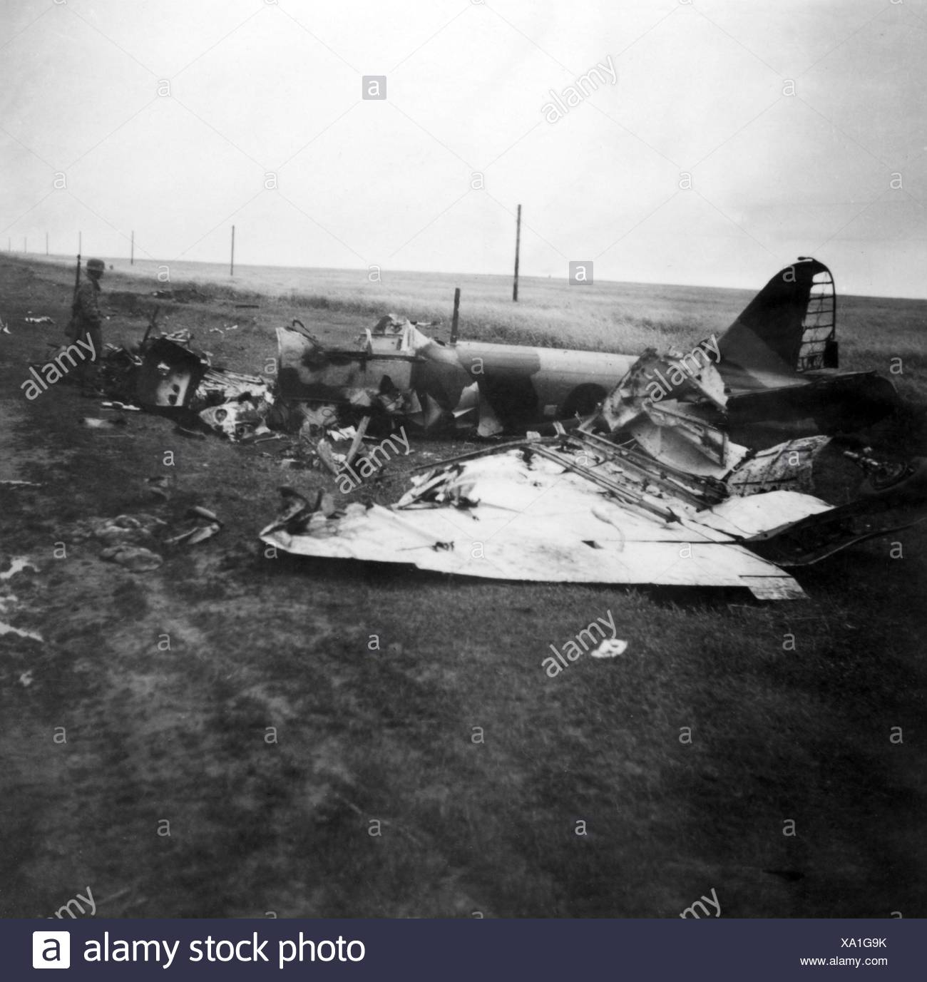 events, Second World War / WWII, aerial warfare, aircraft, crashed / damaged, German soldier standing beside a shot down Soviet ground attack aircraft Ilyushin Il-2, Ukraine, 1941, Additional-Rights-Clearences-Not Available Stock Photo