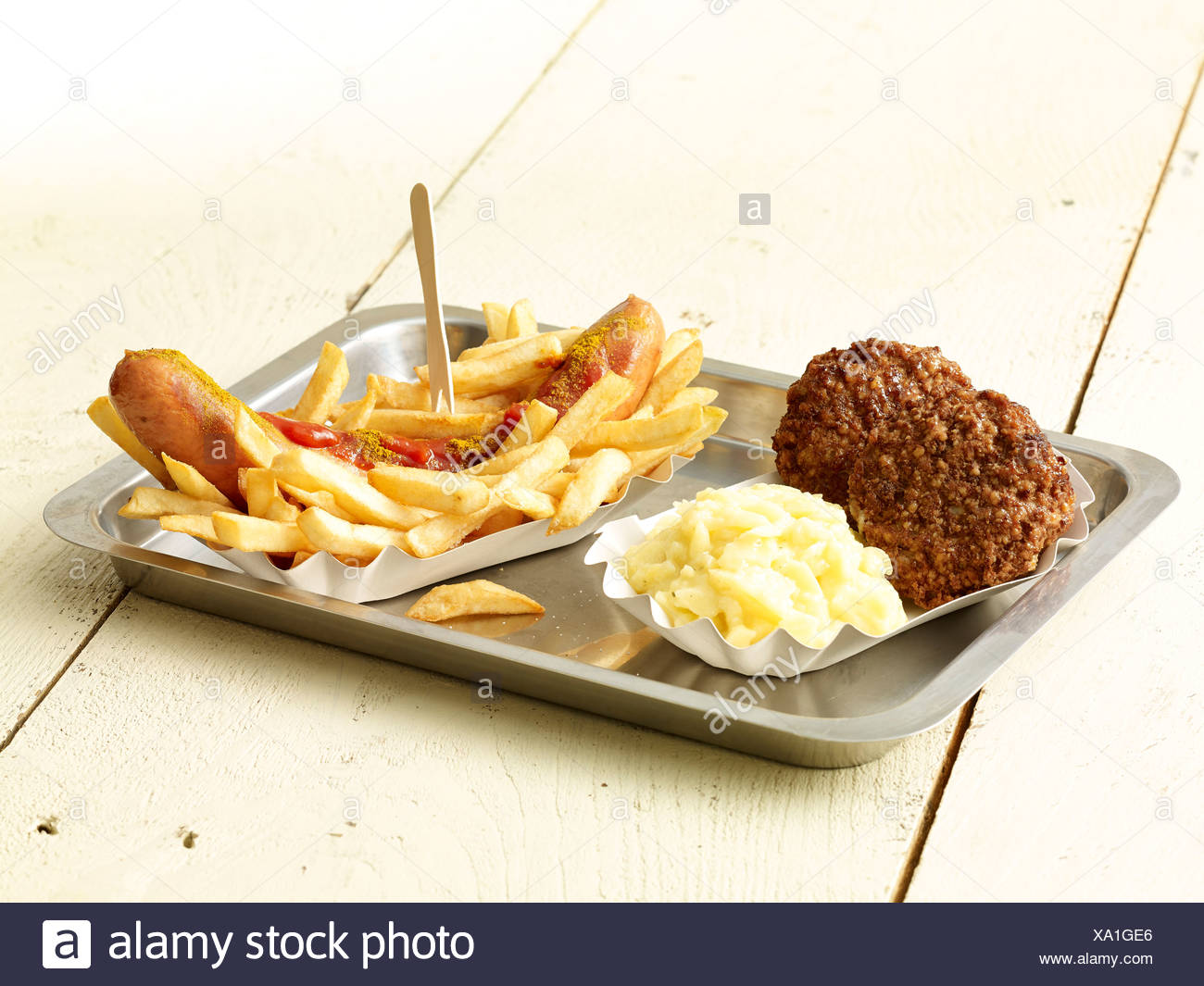 Curry sausage with French fries, two meatballs and mashed potatoes on metal tray Stock Photo