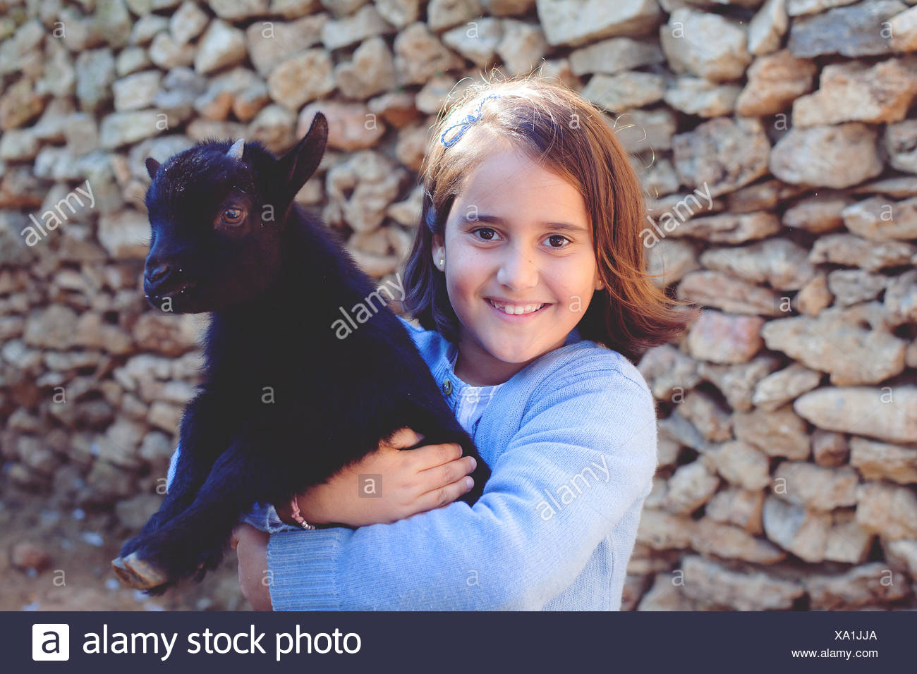 Portrait of girl (6-7) with pet goat - Stock Image