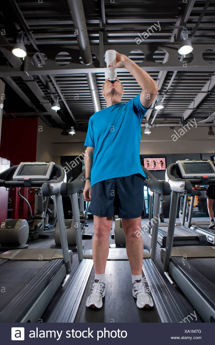Man drinking from water bottle on treadmill in health club - Stock Image