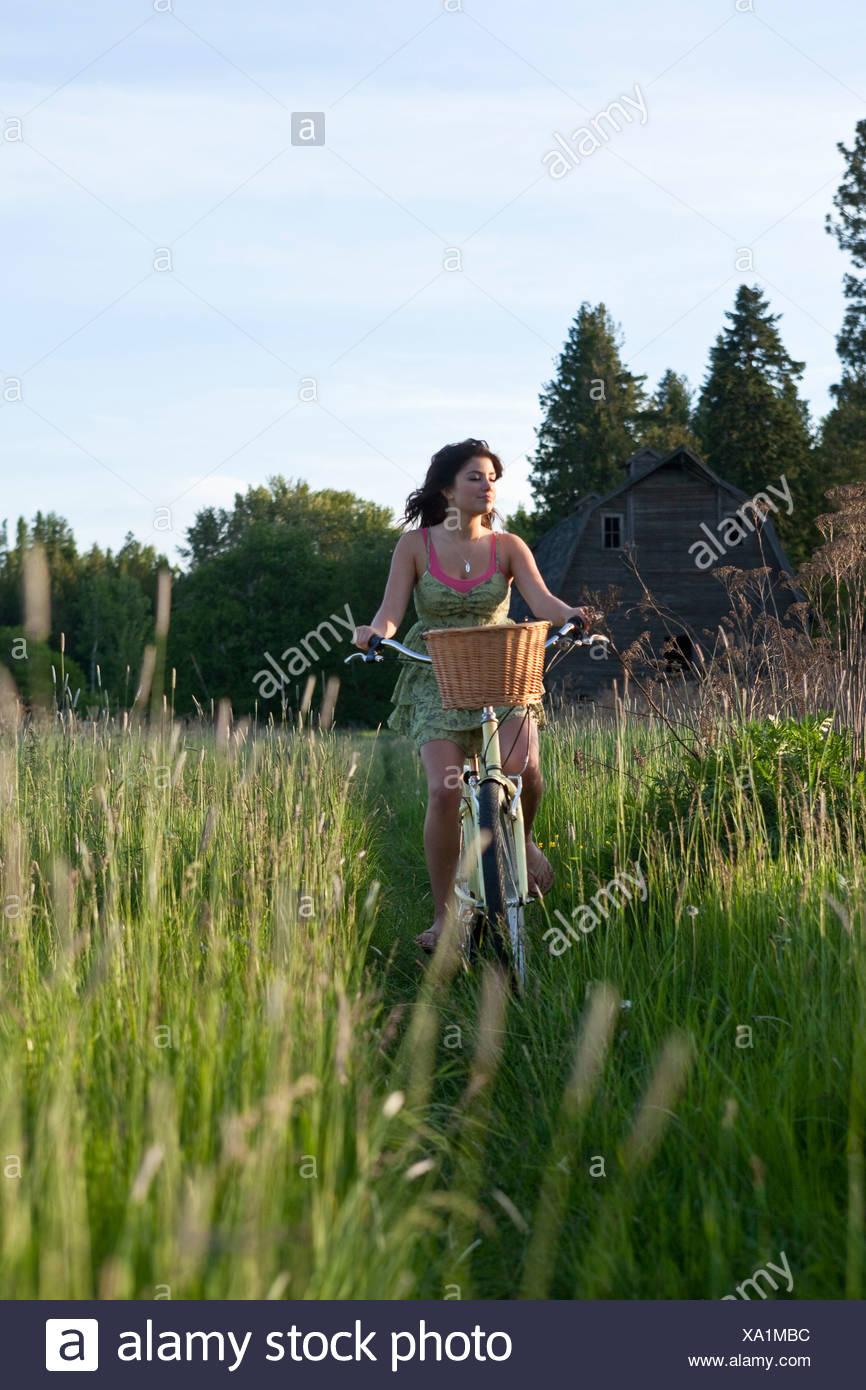Woman rides a beach cruiser down a grassy path in Idaho. - Stock Image