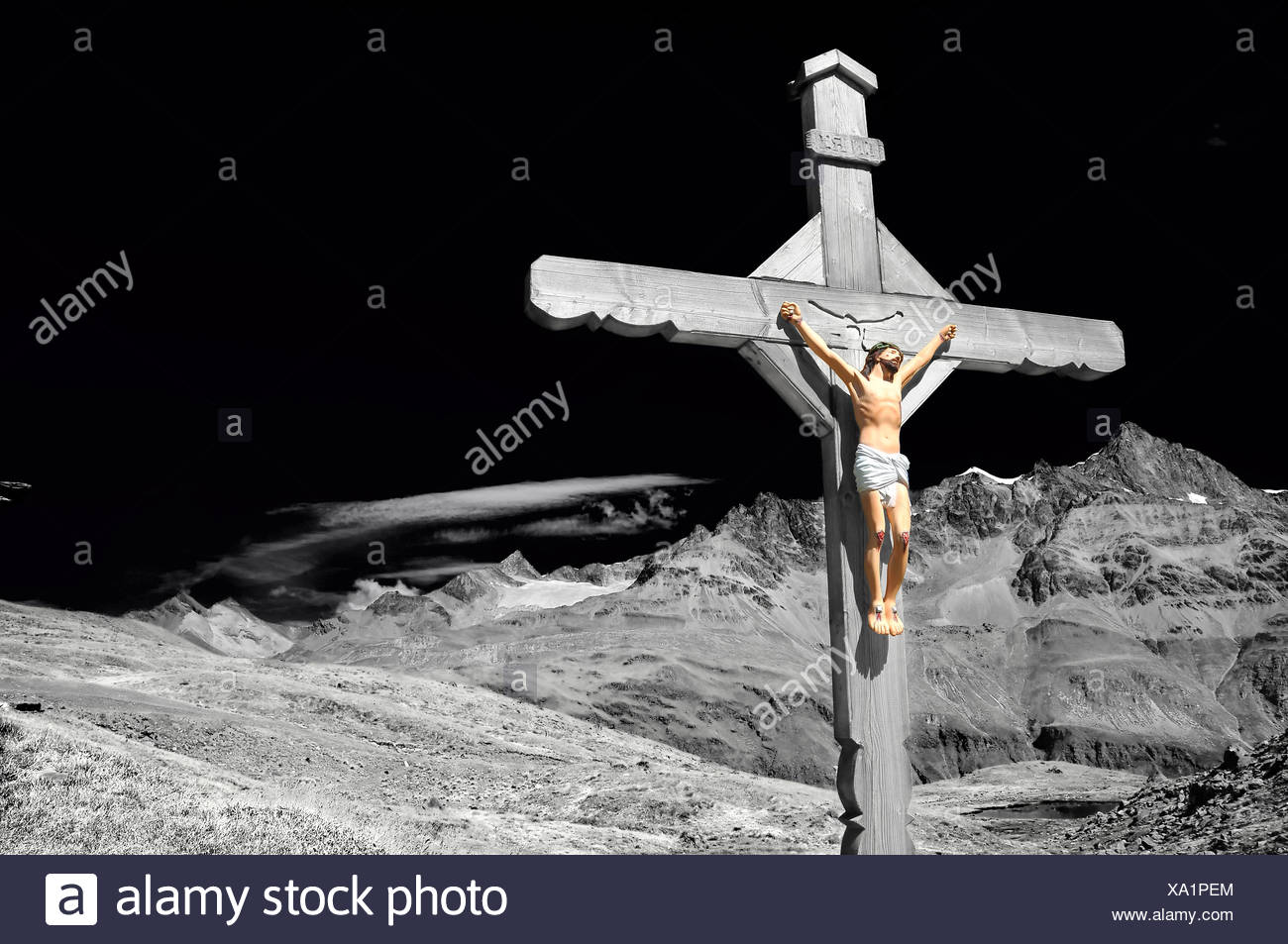 Stunning and dramatic enhanced monochrome cross with jesus christ crucified, in the mountains, above a lake, with high alps in t - Stock Image