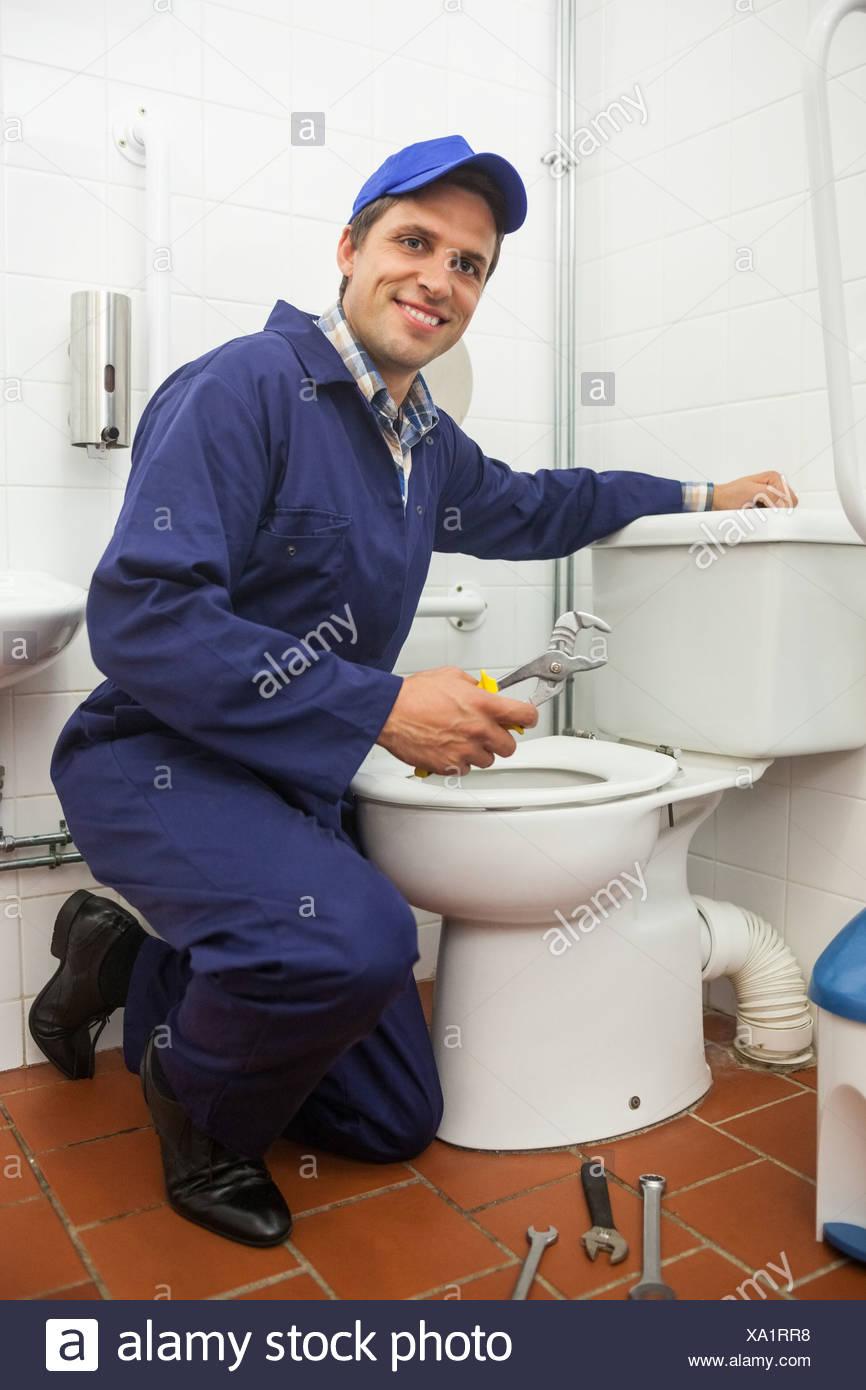 Good looking plumber repairing toilet - Stock Image