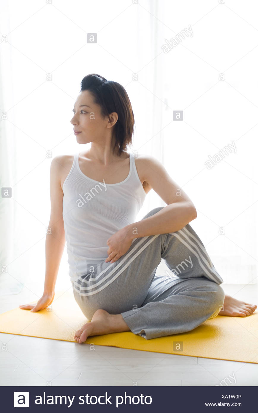 A mid adult woman stretching - Stock Image