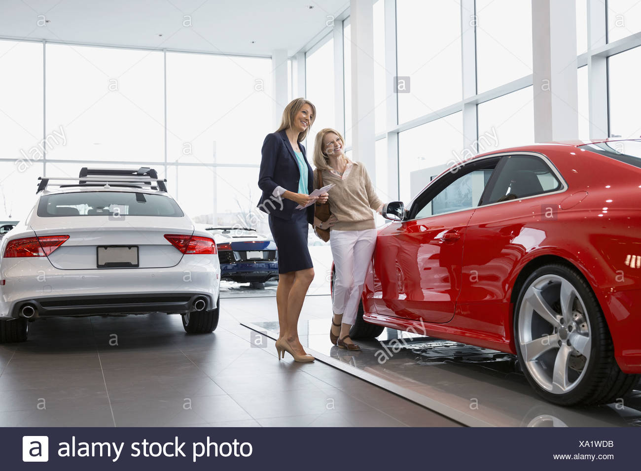 Saleswoman and woman looking at car in showroom - Stock Image