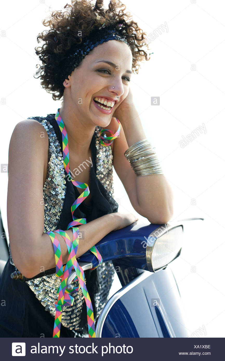 Woman sitting on a scooter after a party - Stock Image