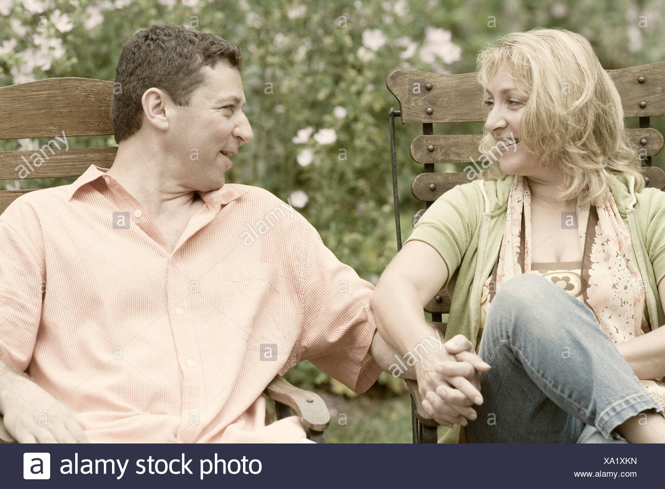 Mature couple sitting on chairs and holding each other's hands Stock Photo