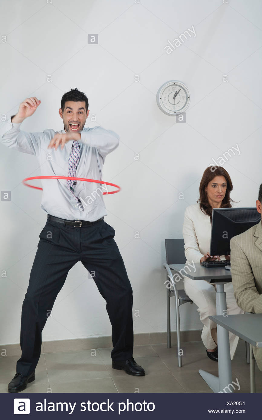 Young businessman playing with hula hoop in office while colleagues work Stock Photo
