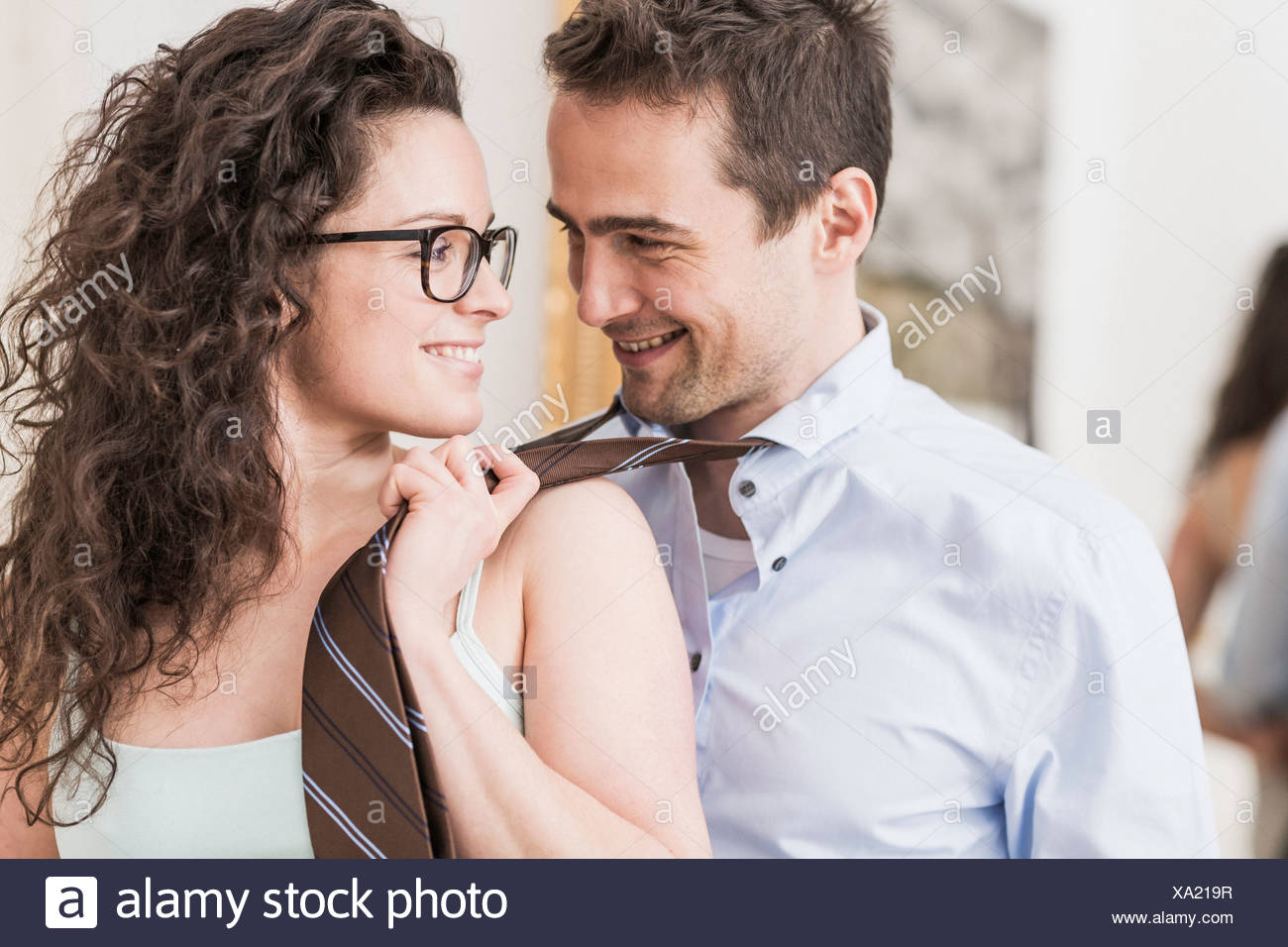 Mid adult woman pulling man's tie - Stock Image