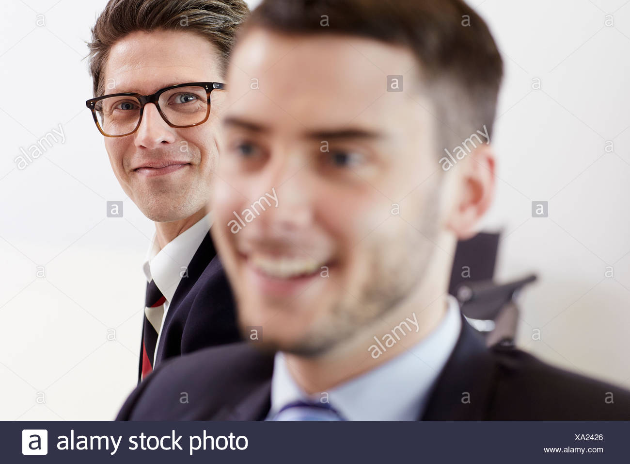 Headshot of businessmen smiling - Stock Image