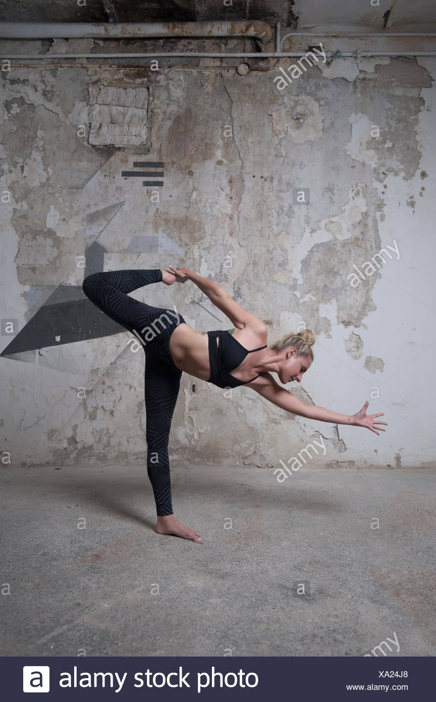 Mid adult woman practicing sugarcane pose in yoga studio, Munich, Bavaria, Germany - Stock Image
